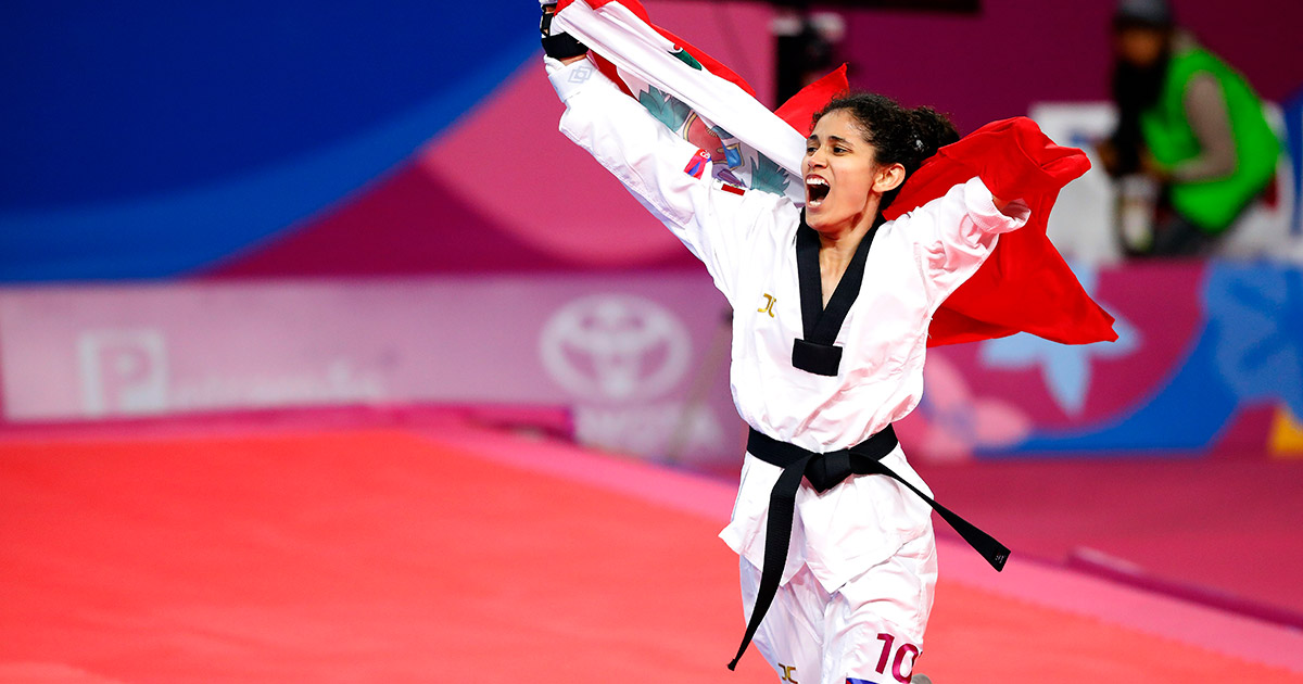 Angélica Espinoza, Peruvian Para athlete, celebrates the gold medal won in Para Taekwondo at Lima 2019 with a flag on her back.