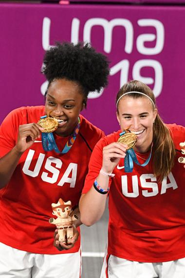 American basketball players Sabrina Ionescu, Olivia Nelson, Ruth Hebard and Christyn Williams bite their gold medals