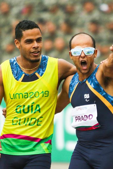Para athlete Lucas Prado and his guide Anderson Machado from Brazil celebrate victory in the Lima 2019 men's 100 m T11 final at the National Sports Village - VIDENA