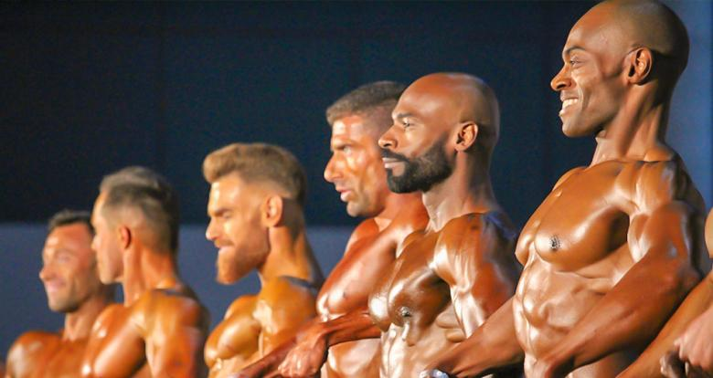Bodybuilders perform a pose during a bodybuilding competition.