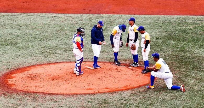 Colombian baseball team groups together in the match for the bronze medal at the Villa María del Triunfo Sports Center during Lima 2019 Games