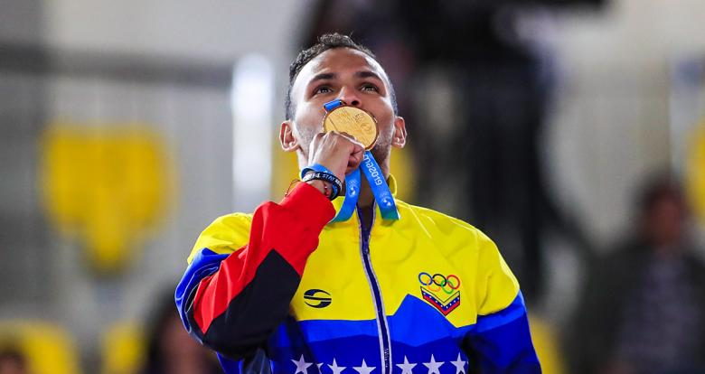 André Madera from Venezuela kisses the gold medal he won in the Lima 2019 Pan American Games karate kumite competition, at the Villa María del Triunfo Sports Center.
