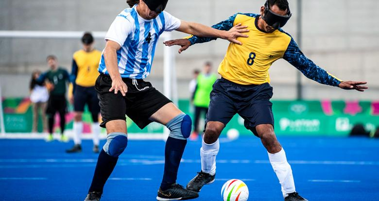 Argentinian Froilan Padila and Brazilian Raimundo de Alves fighting for the ball in Lima 2019 football 5-a-side match at the Villa María del Triunfo Sports Center