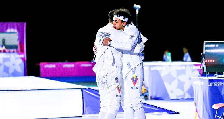 Venezuelan fencers hug at the end of the men's individual épée final at the Lima Convention Center