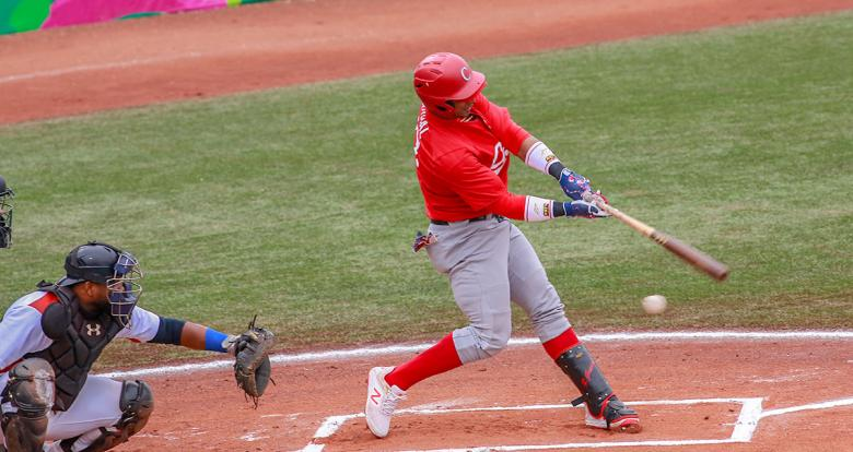 Dominican Miguel Gomez hits the ball against Cuba during Lima 2019 baseball game at Villa María del Triunfo Sports Center