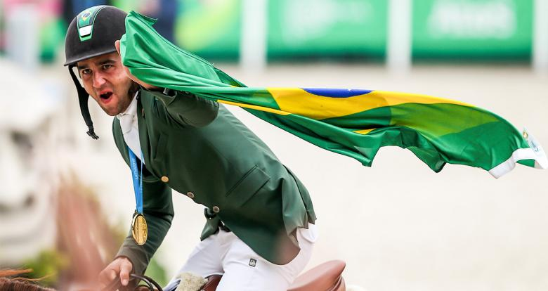 Marlon Zanotelli of Brazil celebrates gold by lifting his flag at the Army Equestrian School
