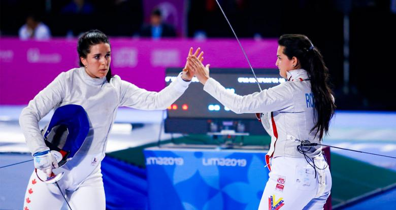 Gabriela Page from Canada and Shia Rodriguez from Mexico high-five each other after fencing competition held at the Lima Convention Center