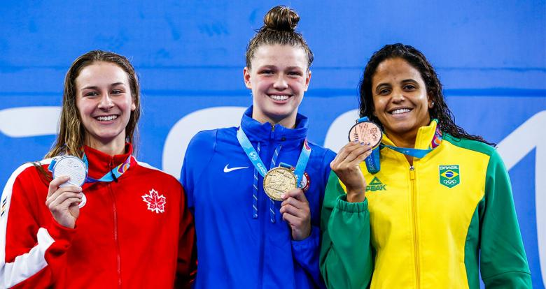 Swimmers Alexia Zevnik from Canada (silver), Margo Greer from the United States (gold) and Larissa Martins de Oliveira from Brazil (bronze) show their medals after competing in women's 100 m freestyle at the National Sports Village – VIDENA