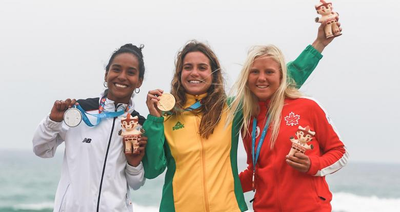 Peruvian Maria Fernandez (silver), Brazilian Chloe Calmon (gold) and Canadian Mathea Dempfle (bronze) celebrate their medals at Lima 2019 Games, in Punta Rocas