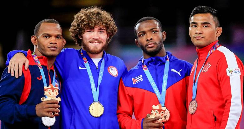 Freestyle wrestling medalists posing on the Lima 2019 podium with their clay cuchimilcos at the Callao Regional Sports Village.