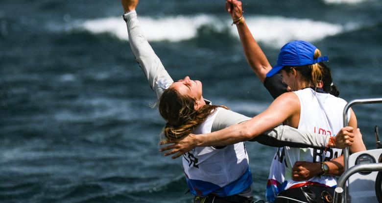 Patrícia Freitas of Brazil (gold), Celia Tejerina of Argentina (silver) and María Bazo of Peru (bronze) hug to celebrate winning their medals in the Lima 2019 women's windsurf competition at Paracas Bay.