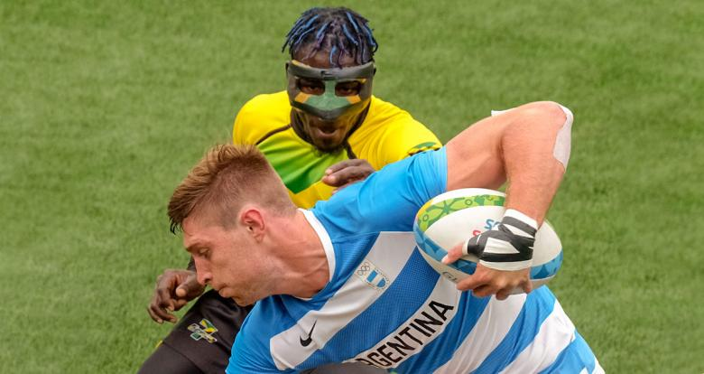 Argentinian Matias Osadczuk holds rugby ball while Jamaican Orlando Edie tries to grab it.