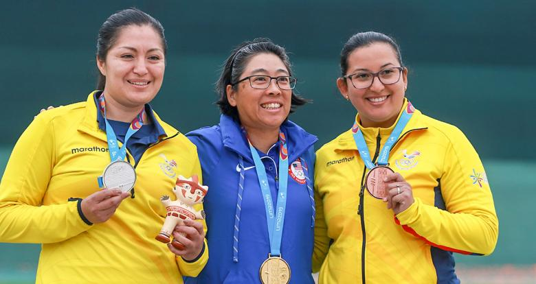 Diana Durango and Andrea Perez from Ecuador (silver and bronze), and Sandra Uptagrafft from the US (gold) posing with their medals of the Women's 25m Pistol competition at Las Palmas Air Base, Lima 2019 Games