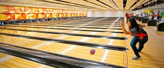 Bowler as she throws the ball down the lane during a bowling championship.