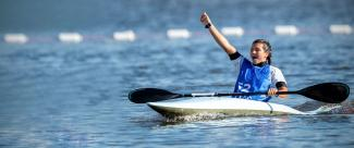 Athlete in her kayak, celebrating his victory in a canoe slalom championship.