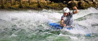 Paddler tries to pass the obstacles in an extreme canoe slalom championship.