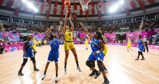 Colombian basketball player Narlyn Mosquera scores a basket vs. Anisha George and Kadesha Barry from Virgin Islands during the Lima 2019 Games at the Eduardo Dibós Coliseum