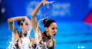 : Laura De Souza and Luisa Nuñez Porto raise their arms in an artistic pirouette at the Lima 2019 Pan American Games