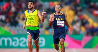Daniel Mendes from Brazil running with his guide Wendel Da Souza during the men's 400 m T11 event at the National Sports Village – VIDENA, Lima 2019
