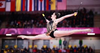 Canadian gymnast Natalie Garcia extending her arms and performing an amazing pirouette at the Villa El Salvador Sports Center in the Lima 2019 Games