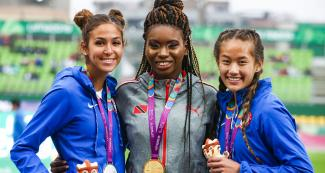 Beatriz Hatz (silver) and Catherine Carey (bronze) from the US, and Nyoshia Cain-Claxton from Trinidad and Tobago (gold) smile with their medals in the Lima 2019 women's 100 m T64 competition at the National Sports Village - VIDENA
