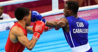 Boxer Duke Ragan from the USA gets punched in the face by Cuban David Caballero in the flyweight category at the Callao Regional Sports Village