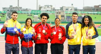 Paula Pereira and her guide Rodrigo Chieregatto from Brazil, Greimal Villarroel and her guide Roberto Medina from Venezuela, and Omara Durand and her guide Yuniol Kindelán from Cuba took the bronze, silver and gold medals, respectively. Para athletes pose with their medals in the Lima 2019 women's 400 m T12 competition at the National Sports Village - VIDENA