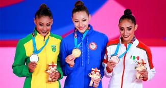 Barbara Domingos, Evita Griskenas, and Karla Díaz, showing her medals at the Villa El Salvador Sports Center