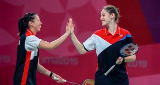Rachel Honderich and Kristen Tsai from Canada share a smile and join hands in a badminton doubles event against Brazil held at the National Sports Village – VIDENA at the Lima 2019 Pan American Games