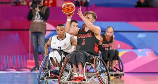 Canadian Robert Hedges holds the ball in his hand as he faces off Colombian Raul Vega in a wheelchair basketball game at the National Sports Village – VIDENA, at Lima 2019