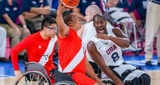 Peruvian Yony Zapata controls the ball while facing off American Brian Bell during a wheelchair basketball game at the National Sports Village – VIDENA, at Lima 2019