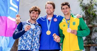 Felipe Borges from Brazil (bronze), Sebastian Rossi from Argentina (silver) and Zachary Lokken from the US (gold) show their medals from the men's C1 category in Río Cañete - Lunahuana