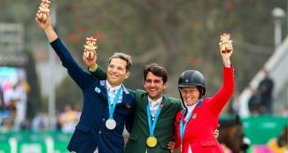 José María Larocca of Argentina (silver), Marlon Zanotelli of Brazil (gold) and Elizabeth Madden of the United States (bronze) proudly posing with their medals and cuchimilco presents after winning in the Lima 2019 jumping event at the Army Equestrian School
