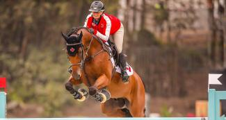 Lisa Anne Carlsen riding her horse during equestrian individual jumping training session at the Army Equestrian School
