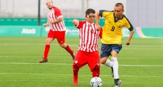 Colombian Camilo Garcia fights for the ball with Peruvian Diego Guzman in football 7-a-side at the Villa María del Triunfo Sports Center, at Lima 2019