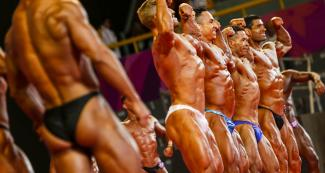 Athletes from around the Americas raising their arms during the Lima 2019 bodybuilding event held at the Chorrillos Military School.