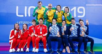 Swimming teams from Canada (silver), Argentina (bronze) and Brazil (gold) show their medals in mixed 4x100 m medley relay held at the National Sports Village – VIDENA