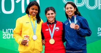 Geiny Pajaro of Colombia (silver), María Moya of Chile (gold) and Dalia Soberanis of Guatemala (bronze) proudly posing with their medals for the women's 300 m time trial at the Lima 2019 Games