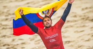 Giorgio Gomez from Colombia holds his flag over his head after his surfing competition at the Lima 2019 Games, in Punta Rocas