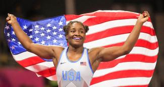 Tamyra Mensah smiling with the U.S. flag after winning the gold medal in Lima 2019 freestyle wrestling event at the Callao Regional Sports Village.