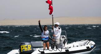 María Bazo of Peru celebrates winning the bronze medal in the Lima 2019 women's windsurf competition at Paracas Bay