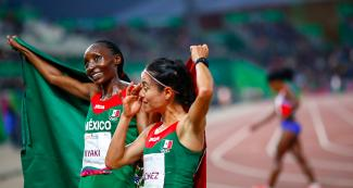 Mexicans Risper Biyaki and Ursula Sanchez celebrate after finishing the athletics final race at the Lima 2019 Pan American Games, at VIDENA