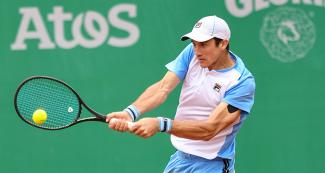Argentinian Facundo Bagnis hits the ball coming from his Brazilian opponent in the men's singles semifinal at the Lima 2019 Games, held at Lawn Tennis Club