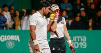 Peruvians Sergio Galdos and Anastasia Iamchkine talking during the mixed doubles match against the Guatemalan pair at the Lawn Tennis Club.