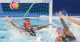 Cuban and Puerto Rican athletes facing off during Lima 2019 water polo competition at the Villa Maria del Triunfo Sports Center.