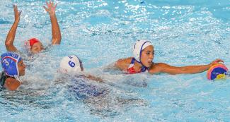 Puerto Rico's Nathalia Melendez and Sabrina Estevez trying to catch the ball during Lima 2019 water polo competition at the Villa Maria del Triunfo Sports Center.