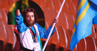 Aruba's delegation walks in at the Lima 2019 Parapan American Games Opening Ceremony flying their national flag at the National Stadium.