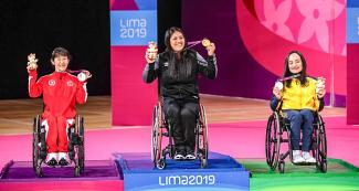Canadian Yuka Chokyu (silver), Peruvian Pilar Jáuregui (gold) and Brazilian Souza (bronze) proudly posing on the Lima 2019 women's WH2 Para badminton podium with their medals, at the Villa El Salvador Sports Center.