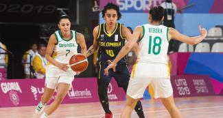 Colombian Mabel Martínez goes up against Brazilians Patricia Teixeira and Débora Fernandes in the Lima 2019 women's basketball game at the Eduardo Dibós Coliseum.