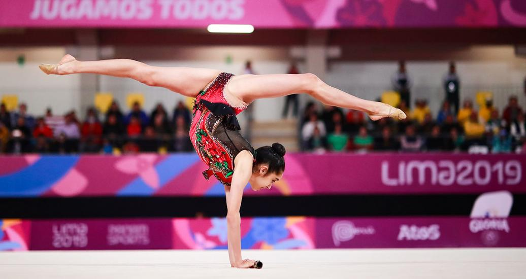 Gymnast Natalie Garcia standing up with her arms and performing an extraordinary pirouette in Lima 2019 Games at the Villa El Salvador Sports Center